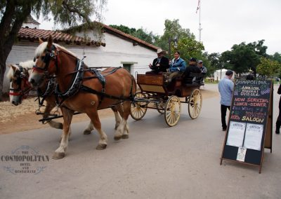 a two horse drawn Carriage in the park with people in the carriage and other walking near display for the restaurant