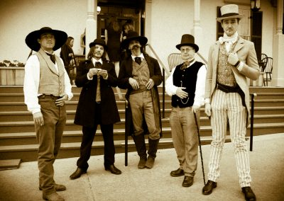men in old west attire standing in front of the steps to the Cosmopolitan hotel and restaurant