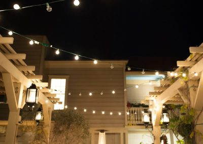 Courtyard at Night with lights strung from pergola to pergola, a fire pit and people enjoying their dinner