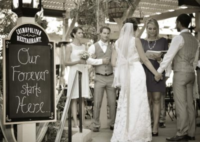 """a wedding ceremony with a sign for the cosmopolitan restaurant """"Our forever starts hers"""""""