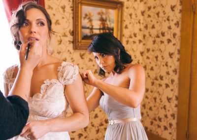a bride receiving makeup and assistance dressing for her wedding
