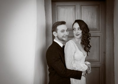 a bride and groom standing in front of a door