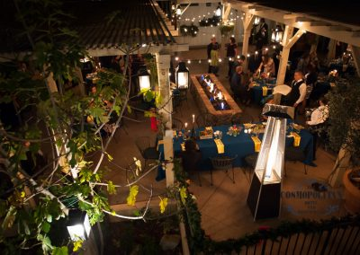 Cosmo courtyard at night with outdoor heaters, a fire pit people being served dinner