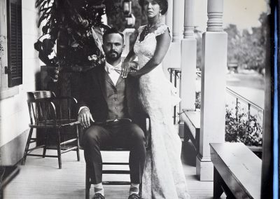 A man sitting and woman standing next to him on a porch