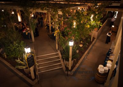 an outdoor wedding venue at night with lamps and dishes ready to serve food