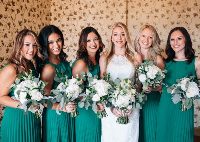 a bride and her bridesmaids holding bouquets of flowers