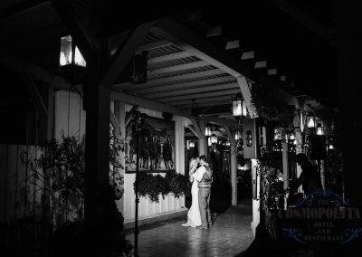 a bride a groom dancing under a pergola at night