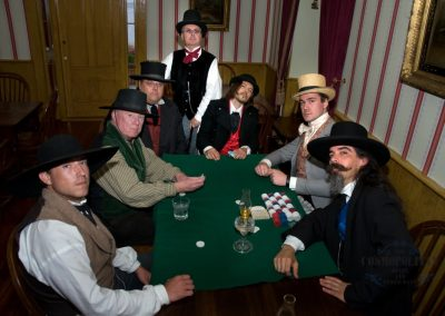 period actors appearing to play cards with poker chips