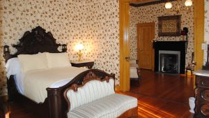 amazing bedroom in western motife with a bed settee and a fireplace in the adjoining room