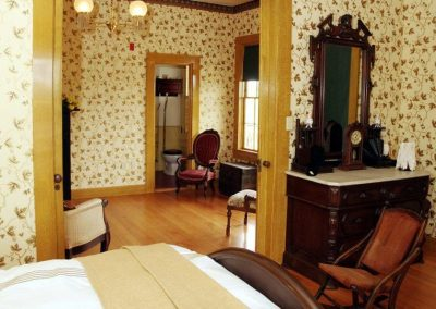 beautiful bedroom decorated in old west with a bed, chairs and lovely side table