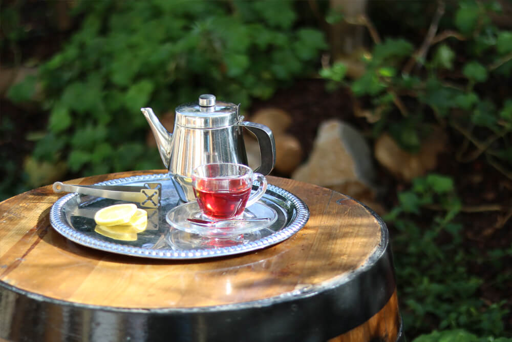 pot and cup of tea setting on silver platter on top of a barrel outside